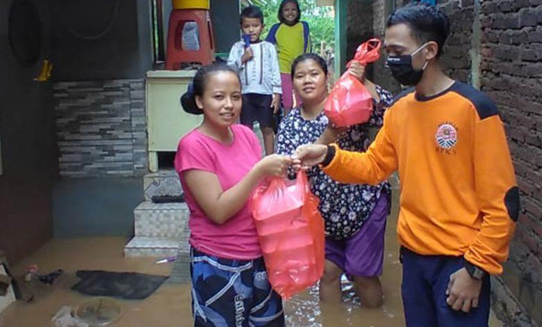 Salah seorang Relawan PKS Sumedang sedang membagikan nasi bungkus kepada warga yang terkena dampak banjir di Cimanggung Sumedang